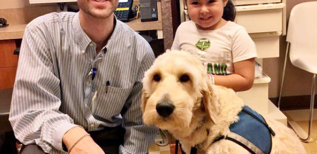 Dr. Evan Los with one of his patients, Sophia, and her diabetes dog St. Nick.