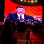 """In this Dec. 3, 2018, photo, a child walks past a large screen showing Chinese President Xi Jinping near a carpark in Kashgar, western China's Xinjiang region. Across the Xinjiang region, a growing number of internment camps have been built, where by some estimates 1 million Muslims are detained, forced to give up their language and their religion and subject to political indoctrination. Now, the Chinese government is also forcing some detainees to work in manufacturing and food industries, in what activists call """"black factories."""""""