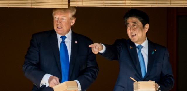 President Donald Trump and Japanese Prime Minister Shinzo Abe speak together while feeding fish at a koi pond at the Akasaka Palace, Monday, Nov. 6, 2017, in Tokyo.