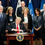 President Donald Trump takes the cap off a pen before signing executive order for immigration actions to build border wall as Vice President Mike Pence, left, and Homeland Security Secretary John F. Kelly, right, and others watch during Trump's a visit to the Homeland Security Department headquarters in Washington, Wednesday, Jan. 25, 2017.
