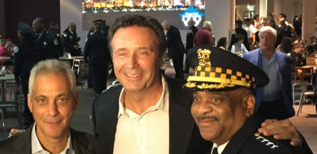 "Former Officer Brian Warner (center) stands next to Chicago Mayor Rahm Emanuel and Police Superintendent Eddie Johnson. Warner plans to fight a police pension board decision to reduce his pension payments and take away his health care coverage after determining his PTSD is ""in remission."""