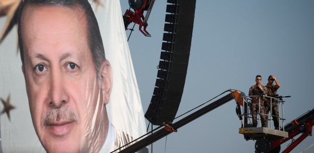 Turkish special forces unit stand on a crane as a giant portrait of Turkish President Recep Tayyip Erdogan is hanged over a Democracy and Martyrs' Rally in Istanbul, Sunday, Aug. 7, 2016. A massive crowd of flag-waving supporters gathered in Istanbul Sunday for a giant rally to mark the end of nightly demonstrations since Turkey's July 15 abortive coup that left more than 270 people dead.