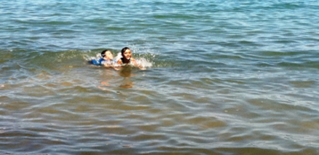 Children take a dip in Lake Michigan at Oak Street Beach despite the bacteria advisory.