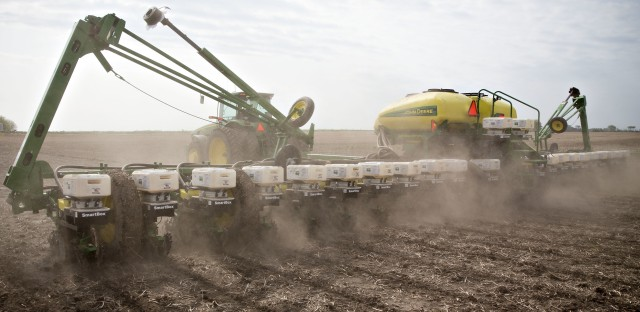 A tractor pulls a planter while distributing corn seed on a field in Malden, Ill. Two scientists agree that pesticide-laden dust from planting equipment kills bees. But they're proposing different solutions, because they disagree about whether the pesticides are useful to farmers.