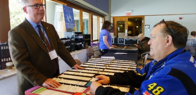 Kellerman talks to a customer at the American Stamp Dealers Association's show in Lombard.