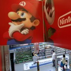 In this May 7, 2014, file photo, shoppers walk under the logo of Nintendo and Super Mario characters at an electronics store in Tokyo.