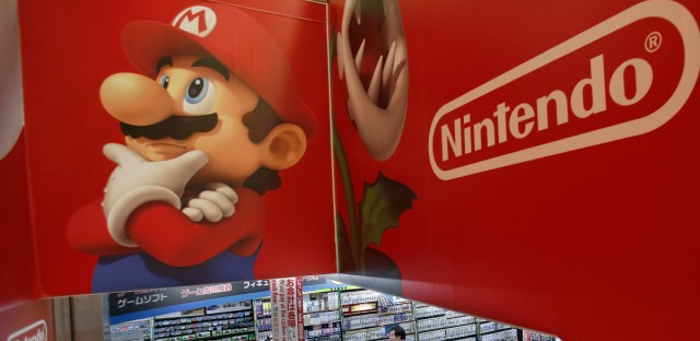 In this May 7, 2014, file photo, shoppers walk under the logo of Nintendo and Super Mario characters at an electronics store in Tokyo. How much yen did Nintendo pay to land that dream marketing opportunity at the Rio Olympics closing ceremony when Japan's prime minister popped out dressed as the red-hatted plumber Super Mario? Zero. The video game character Mario is coming to iPhones. CEO Tim Cook said the popular Japanese game had been missing until now.