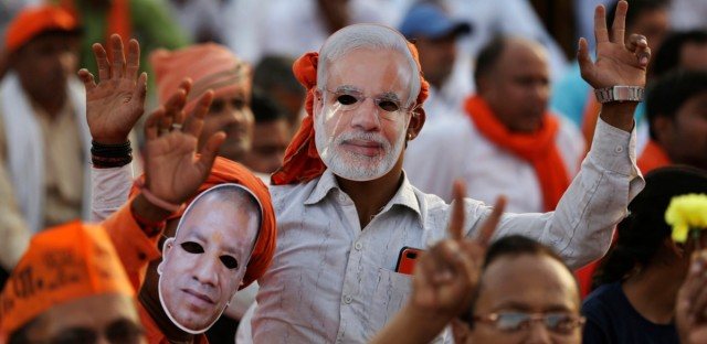 Bharatiya Janata Party (BJP) supporters wear masks of Indian Prime Minister Narendra Modi, center and Uttar Pradesh Chief Minister Yogi Adityanath, left,during an election rally in Prayagraj, India, Monday, April 29, 2019.