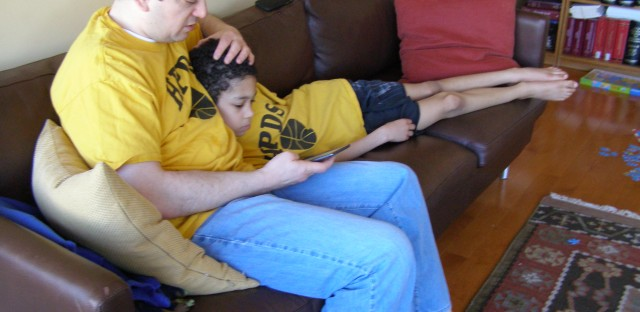 David Forst and his son Jacob read Tom Sawyer off their Kindle in their Chicago home.