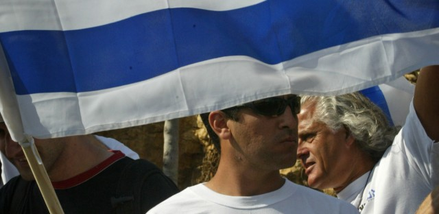 An Israeli, wearing a shirt with an image of Theodor Herzl, the founder of modern Zionism, carries a national flag as he marches in a protest near Jerusalem on May 1, 2017.