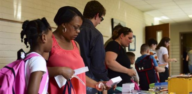 Parents help their children select school supplies during a back-to-school event.