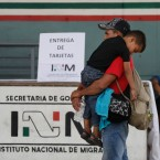 A Central American migrant carries a child as he waits for his humanitarian visa from Mexican migration officials to be processed, on the border between Mexico and Guatemala, near Ciudad Hidalgo, Chiapas state, Mexico, Sunday, Jan. 20, 2019. Many Central American migrants are waiting for Mexican officials to issue them humanitarian visas, which give them permission to be in Mexico for one year.