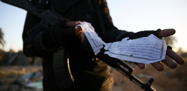 In this Feb. 20, 2016, file photo, a member of the Libyan security forces displays part of a document in Arabic describing weaponry, that was found at the site of U.S. airstrikes on an Islamic State camp that killed dozens, near the western city of Sabratha, Libya. The work of photographer and video journalist Mohamed Ben Khalifa, who was killed in Libya on Saturday, Jan. 19, 2019, reflected Libya's post-2011 chaos of rival militias fighting for control as well as the humanitarian tragedy of waves of people fleeing North Africa, the Middle East and sub-Saharan Africa.