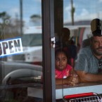 A man and girl peer out from a bakery and cafeteria in Freeport, Bahamas, Wednesday, Sept. 11, 2019. Those who survived Hurricane Dorian are facing the prospect of starting their lives over but with little idea of how or where to even begin.