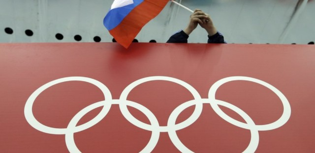 A Russian skating fan holds the country's national flag over the Olympic rings before the start of the men's 10,000-meter speedskating race at Adler Arena Skating Center during the 2014 Winter Olympics in Sochi, Russia.