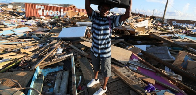 A man carries clothes over what remains of homes in the area called The Mudd after it was devastated by Hurricane Dorian, as he prepares to evacuate Abaco Island, Bahamas, Sunday, Sept. 8, 2019. Dorian was the most powerful hurricane in the northwestern Bahamas' recorded history.