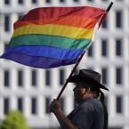 Paco Garcia, of San Antonio, Texas, waves a rainbow flag in memory of the victims of the 2016 Pulse nightclub shooting, in Orlando, Fla. Eric Gay/AP