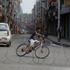 "An Indian boy rides a bicycle past a barbed wire erected as part of security restrictions in Jammu, India, Tuesday, Aug.6, 2019. India's lower house of Parliament was set to ratify a bill Tuesday that would downgrade the governance of India-administered, Muslim-majority Kashmir amid an indefinite security lockdown in the disputed Himalayan region. The Hindu nationalist-led government of Prime Minister Narendra Modi moved the ""Jammu and Kashmir Reorganization Bill"" for a vote by the Lok Sahba a day after the measure was introduced alongside a presidential order dissolving a constitutional provision that gave Kashmiris exclusive, hereditary rights."