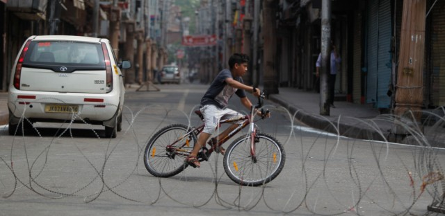 A boy rides a bicycle past a barbed wire erected as part of security restrictions in Jammu, India, Tuesday, Aug.6, 2019.