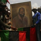 Men hold a portrait of Dim Chukwuemeka Ojukwu in Nnewi, Nigeria on Wednesday, Feb. 29, 2012. The city where Biafra leader Dim Chukwuemeka Ojukwu lived is preparing for the burial of the civil war leader at his home here on Friday. Nigeria's 1960s civil war, between the federal government and Ojukwu's breakaway Republic of Biafra, killed 1 million people. (AP Photo/Jon Gambrell)