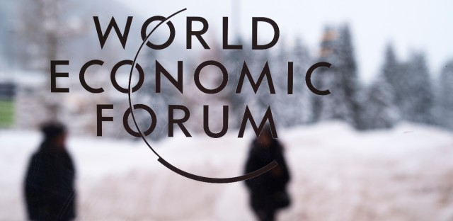 Two people walk behind the logo of the World Economic Forum at the meeting's conference center in Davos, Switzerland, Sunday, Jan. 21, 2018.