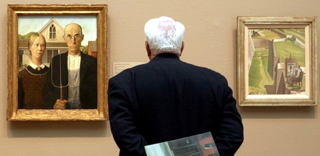 A visitor looks at Grant Wood's American Gothic, left, Wednesday, April 13, 2005, in the new American Art galleries at the Art Institute of Chicago.