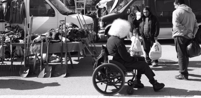 A man in a wheelchair visits a vendor on Maxwell Street.