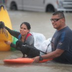 People make their way out of a flooded neighborhood in Houston on Monday. Many people are turning to social media for help.