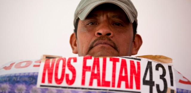 "A man holds up a photograph of a missing student with a caption reading ""We are missing 43,"" during a press conference by the parents of missing teachers college students in response to a report issued Sunday by the Inter-American Commission on Human Rights expert group in Mexico City, Monday, April 25, 2016. There is strong evidence that Mexican police tortured some of the key suspects arrested in the disappearance of 43 students, according to the report. The group also complained the government was slow to deliver some of the evidence it had asked for and criticized government prosecutor's investigations as flawed and incomplete."