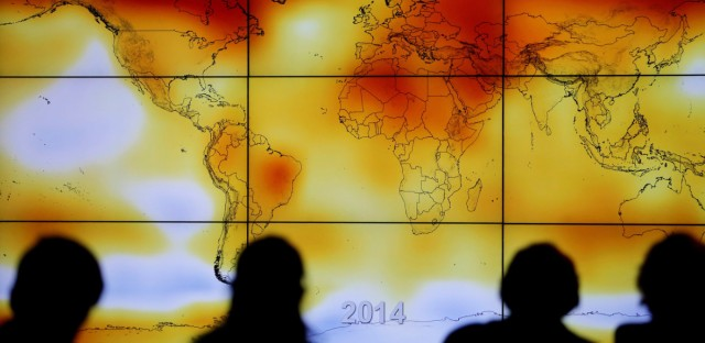 Participants look at a world map with climate anomalies during the World Climate Change Conference 2015 in France. A draft government report on climate, which was leaked ahead of publication, says the U.S. is already experiencing the consequences of global warming.