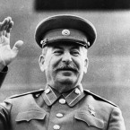 A smiling General Joseph V. Stalin raises his right hand in salute while reviewing a May Day Parade, in Moscow, May 1, 1946. Photo from Russian film.