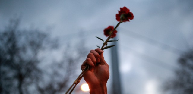 "A person holds up a carnation as people gather at the nightclub, the scene of the New Year's Day attack, in Istanbul, Tuesday, Jan. 3, 2017. The Islamic State group claimed responsibility for the attack killing 39 people saying a ""soldier of the caliphate"" had carried out the mass shooting to avenge Turkish military operations against IS in northern Syria."