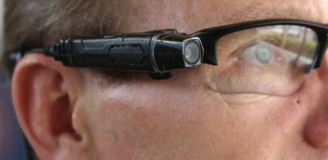 In this photo taken Thursday, Feb. 19, 2015, Steve Tuttle, vice president of communications for Taser International, demonstrates one of the company's body cameras that can be attached to glasses , for the Associated Press during a company-sponsored conference hosted by Taser at the California Highway Patrol Headquarters in Sacramento, Calif. Taser, the stun-gun maker, has become a leading supplier of body cameras for police and has cultivated financial ties to police chiefs whose departments have bought the recording devices. A review by The Associated Press shows Taser is covering airfare and hotel stays for police chiefs who travel to speak at the company's marketing conferences. It is also hiring some recently retired chiefs as consultants, sometimes months after their cities signed contracts with Taser.