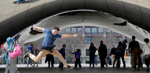 Visitors to Millennium Park enjoy warm weather as they inspect the park's Cloud Gate sculpture Monday, April 13, 2015, in Chicago.