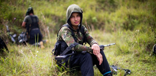 """In this Jan. 6, 2016 file photo, Juliana, a 20-year-old rebel fighter for the 36th Front of the Revolutionary Armed Forces of Colombia, or FARC, rests from a trek in the northwest Andes of Colombia, in Antioquia state. On year after the Nov. 24 2016, peace accords between the Colombian government and the FARC rebels, Bernard Aronson, who served as President Barack Obama's special envoy to the peace talks, said that even if Colombia misses the historic opportunity to integrate its lawless countryside with the more prosperous cities """"the war is over and nobody thinks it will restart again."""""""