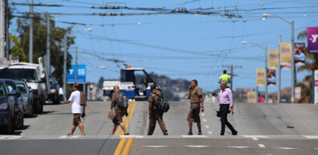 UPS employees cross 16th Street shortly after a shooting at the company's facility in San Francisco.