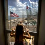 "FILE - In this Aug. 14, 2015 file photo, a girl looks out from the newly opened U.S. Embassy after the U.S. flag raising ceremony in Havana, Cuba, as part of officially restored diplomatic relations. U.S. presidential candidate Donald Trump had been generally supportive of the normalization of relations with Cuba, but on Friday, Sept. 16, 2016 the Republican nominee pledged to reverse Obama's series of executive orders unless Cuba's President Raul Castro meets demands including ""religious and political freedom for the Cuban people and the freeing of political prisoners."""