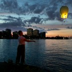 Elizabeth Hinker of Chicago, releases a Japanese Wish Lantern during sunset over Lake Michigan from the city's Promontory Point Park in the Hyde Park neighborhood Saturday, Sept. 14, 2019.