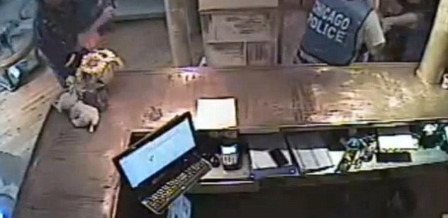 A still from a surveillance video showing the 2013 police raid of a Chicago tanning salon managed by Jessica Klyzek (right).