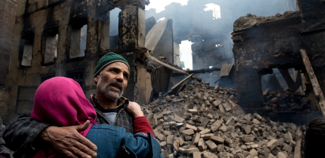 A Kashmiri woman comforts a wailing relative after his house was destroyed in a gunbattle in Tral village, south of Srinagar, Indian controlled Kashmir, Tuesday, March 5, 2019. Two suspected rebels were killed in a gunbattle with Indian forces in Indian-controlled Kashmir, police said Tuesday.