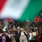 Standing next to his wife Beatriz Gutierrez Muller, right center, Mexico's newly sworn-in President Andres Manuel Lopez Obrador holds up a chieftain's staff during a traditional indigenous ceremony at the Zocalo, in Mexico City, Saturday, Dec. 1, 2018. Lopez Obrador was formally anointed leader by indigenous groups at the ceremony. Mexico has more than 70 indigenous communities, and Lopez Obrador has pledged to end centuries of poverty and marginalization for them.