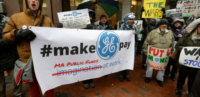 Protesters display placards outside the location of a news conference by General Electric CEO Jeff Immelt, Massachusetts Gov. Charlie Baker, and Boston Mayor Marty Walsh, Monday, April 4, 2016, in Boston. The protest was held to highlight the millions of dollars in tax breaks and public incentives, including the prospect of free rent on city-owned land, used to lure the company to the city.