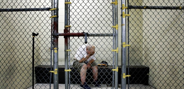 FILE - In this June 26, 2014 file photo, a U.S. veteran with post-traumatic stress sits in a segregated holding pen at the Cook County Jail after he was arrested on a narcotics charge in Chicago. Cook County plans to open a 24-hour triage center on the far South Side of Chicago where police can drop off people experiencing psychiatric or substance-abuse crises. The goal is ease pressure on the jail, where 1 in 5 detainees is locked up because of mental health problems. (AP Photo/Charles Rex Arbogast-File)
