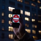 """A protester supporting Apple in its battle against the FBI holds up an iPhone that reads """"No Entry"""" outside an Apple store in New York on Feb. 23."""