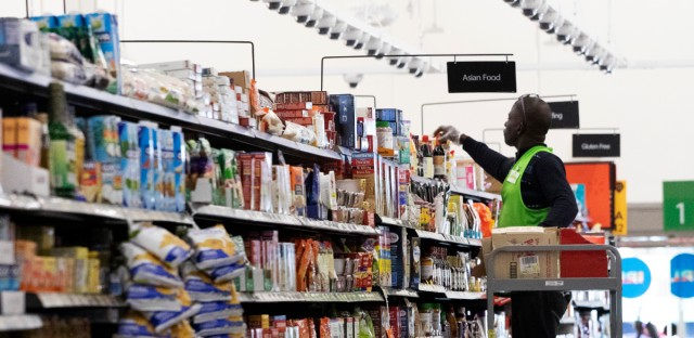 In this April 24, 2019, file photo a Walmart associate arranges items on a shelf at a Walmart Neighborhood Market in Levittown, N.Y. Walmart Inc. reports earnings on Thursday, May 16