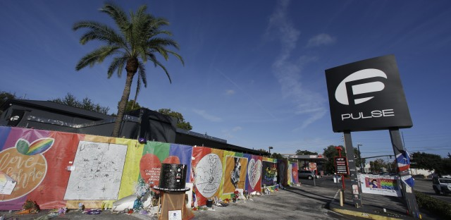 Artwork and signatures cover a fence around the Pulse nightclub in Orlando, Fla., on Nov. 30, 2016.