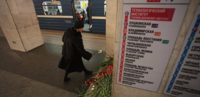 People lay flowers at the Technology Institute subway station in St. Petersburg, Russia, Tuesday. Federal investigators say they found remains of the man they believe carried out the attack in the subway train.