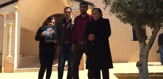 Georgette Melki and her surviving children hold a picture of her son, who was one of at least three people killed after ISIS overran a string of Assyrian Christian villages last year.