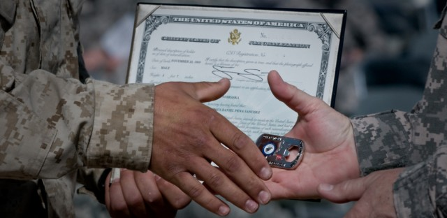 A U.S. Marine receives his Certificate of Naturalization and a command coin from Army Maj. Gen. Timothy McHale, deputy commander of support for U.S. forces in Afghanistan, during a naturalization ceremony at Kandahar Airfield, Afghanistan, Oct. 1, 2010.