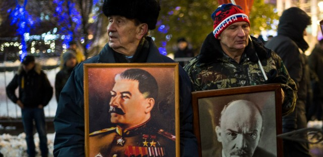 Two men hold portraits of Soviet dictator Josef Stalin, left, and Soviet Founder Vladimir Lenin during a demonstration marking the 99th anniversary of the 1917 Bolshevik revolution in Moscow, Russia, Monday, Nov. 7, 2016. Unlike the past, Nov. 7 is no longer a public holiday in Russia.